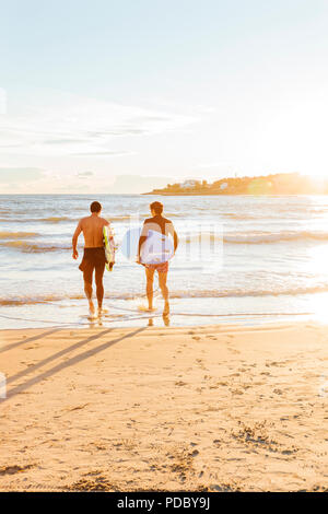 Homme surfers carrying surfboards dans océan sur sunny beach Photo Stock