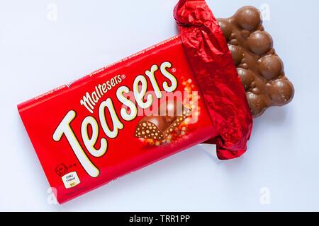 Maltesers réflexion barre de chocolat ouvert pour afficher contenu situé sur fond blanc - peu croquants Maltesers morceaux flottant dans le chocolat au lait crémeux Photo Stock