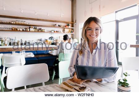 Portrait woman looking at menu dans cafe Photo Stock