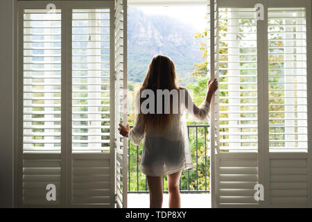 Vue arrière du Caucasian woman standing by door at home Photo Stock