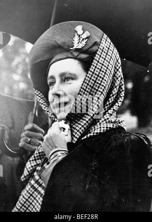 Elizabeth Bowes-Lyon, la reine consort, met un foulard sur son chapeau contre les fortes pluies. Photo Stock