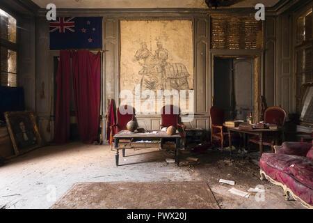 Vue intérieure d'un salon avec des meubles anciens et une collection d'objets historiques dans un château abandonné en France. Photo Stock