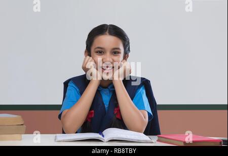 Portrait de jeune fille rurale en uniforme d'sitting at table Photo Stock