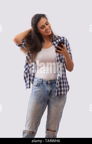 Woman looking at mobile phone en touchant ses cheveux Photo Stock