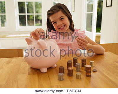 Girl putting coins en piggy bank Photo Stock