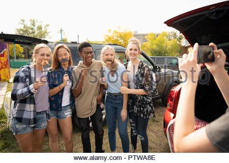 Les adolescents ludique posant avec moustache accessoires Photo Stock
