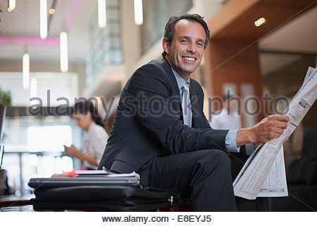 Businessman reading newspaper in hotel lobby Photo Stock