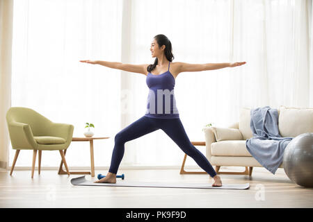 Cheerful pregnant woman practicing yoga at home Photo Stock