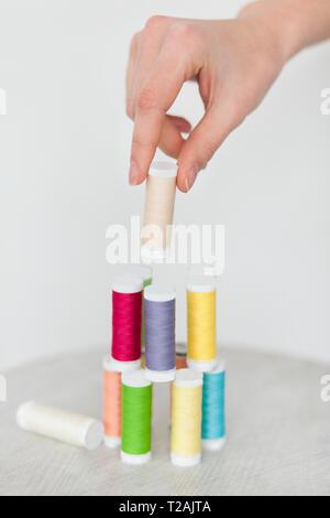 Main de femme de couleur d'empilage des bobines de fil Photo Stock