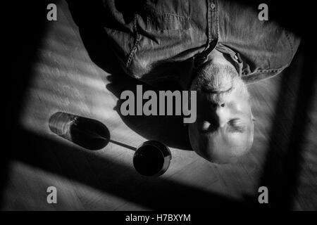 Vieil homme se reposant sur le sol. Portrait en noir et blanc avec des ombres profondes. Image conceptuelle de la Photo Stock