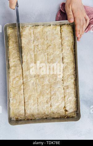 Woman making baklava aux noix dans une plaque à pâtisserie Photo Stock