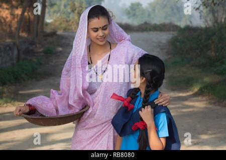 Female farmer ou rural femme marche sur village-rue, avec sa fille va à l'école portant un fer à repasser gold pan. Photo Stock