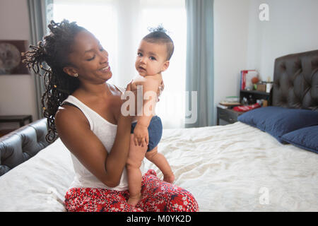 Mother sitting on bed holding baby daughter Photo Stock