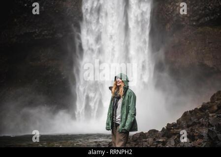 Female hiker in rain jacket à cascade, Whistler, British Columbia, Canada Photo Stock