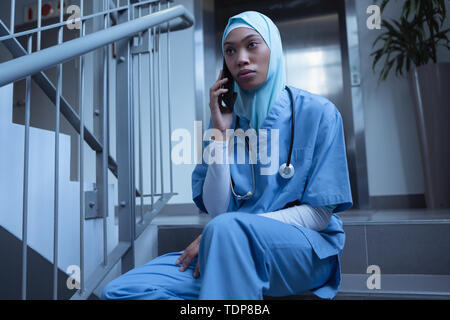 Vue avant de race mixte infirmière en hijab talking on mobile phone while sitting on stairs at hospital Photo Stock