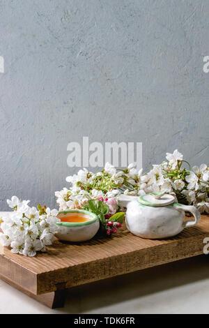 Fait main artisanat théière et tasse en céramique avec du thé chaud décoré par des branches de cerisier en fleurs au printemps sur le plateau de service en bois de style japonais sur blanc en t Photo Stock