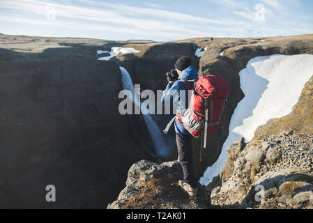 Hiker with backpack sur falaise par Haifoss cascade en Islande Photo Stock