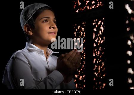 Jeune garçon musulman wearing cap priant dans le noir à l'écart et souriant Photo Stock