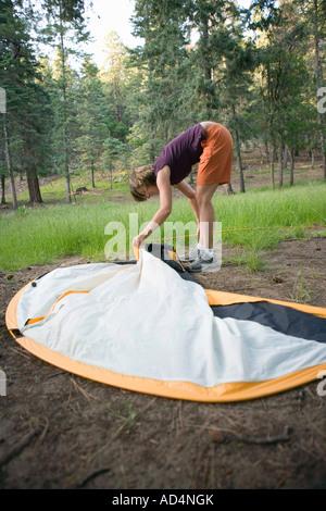 Une femme mise en place d'une tente Photo Stock