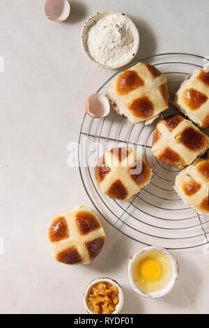 Traditionnel de Pâques faits maison les brioches sur une grille avec des ingrédients ci-dessus sur fond de marbre blanc. Vue de dessus, de l'espace Photo Stock