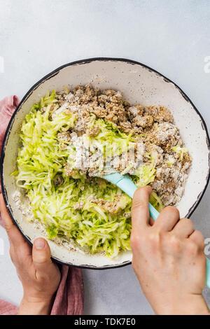 Woman folding déchiquetés les courgettes en les ingrédients secs dans un bol en céramique. Photo Stock