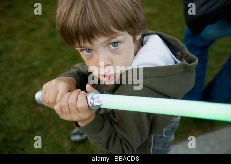 Un jeune garçon tenant une épée-jouet Photo Stock