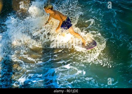 Jeune garçon surfant sur les vagues de l'océan au coucher du soleil. © Myrleen Pearson .....Ferguson Cate Photo Stock