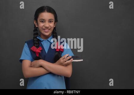 Portrait d'école rurale Girl standing in front of blackboard Photo Stock