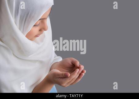 Jeune musulmane de prier avec les yeux fermés Photo Stock