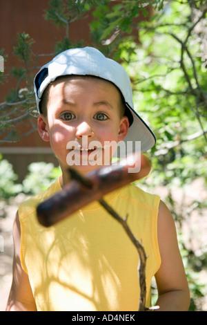 Un jeune garçon tenant une saucisse cuite sur un bâton Photo Stock