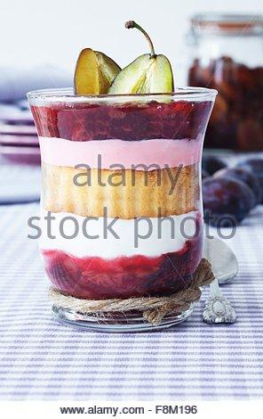Un dessert composé de génoise, compote de quark et servi dans un verre Photo Stock