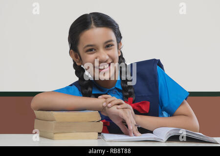 Portrait de school girl leaning on books at table Photo Stock