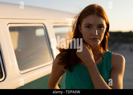 Portrait of beautiful young Caucasian woman looking at camera près de camping-van at beach Photo Stock