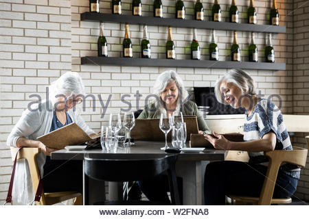 Les femmes âgées à la recherche d'amis à menu au restaurant Photo Stock