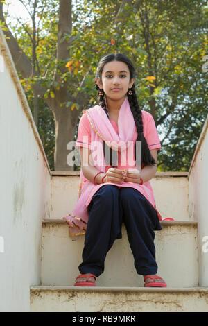 Jeune villageoise assise sur les marches de sa maison donnant sur la terrasse. Photo Stock