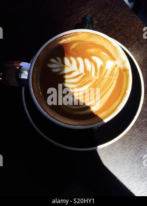 Tasse de café, partiellement à l'ombre, avec un design de fougère sur la mousse Photo Stock