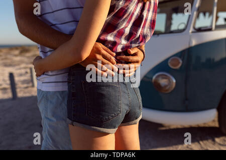 Mid section of young Caucasian couple près de camping-van at beach Photo Stock