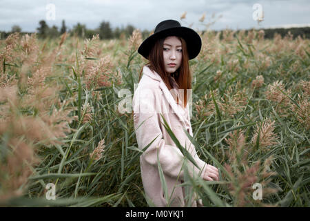 Asian woman standing in field Photo Stock