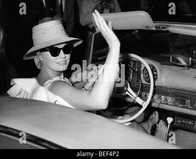 L'actrice suédoise Anita Ekberg vagues en conduisant une voiture décapotable. Photo Stock