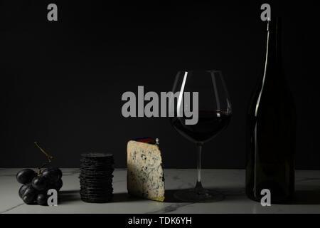 Vin et fromage, avec des craquelins et des raisins sur une surface de carreaux de marbre. Photo Stock
