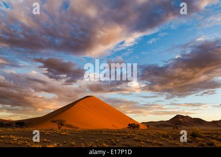 Lever de soleil sur une dune de sable avec des nuages au-dessus de.Soussvlei.La Namibie Photo Stock