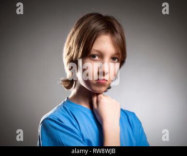 Portrait d'un garçon en haut bleu à la recherche, la pensée. Photo Stock