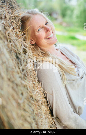 Woman leaning on haybale Photo Stock
