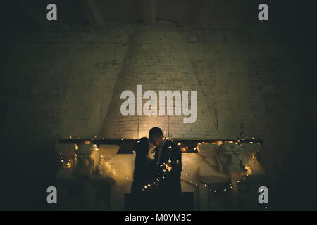 String lights sur Caucasian couple près de cheminée Photo Stock