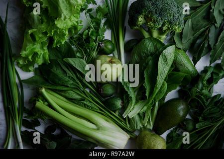Aliments verts frais, variété de légumes, fruits et verts sur surface en marbre. Concept de saine alimentation. Idée monochromatique. Photo Stock
