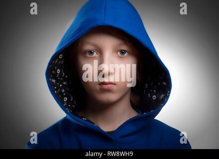 Portrait d'un garçon avec les cheveux bruns en bleu le capot. Photo Stock