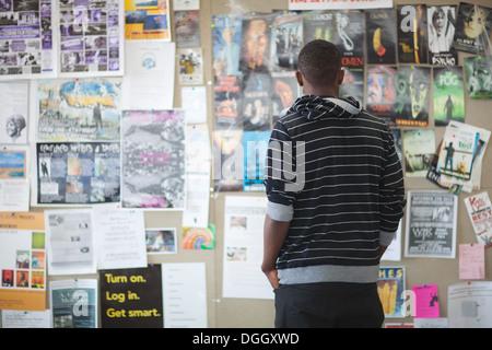 Dix-huit ans, se penche sur un babillard dans cafétéria du collège rempli d'offres d'emploi, les programmes de cinéma, horaire de l'événement. Photo Stock