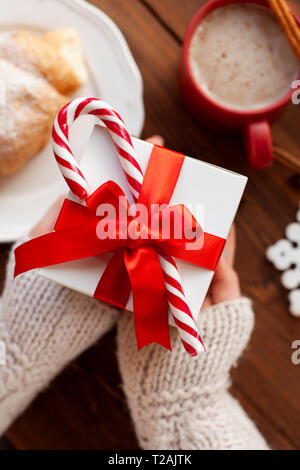 Mains de woman holding Christmas present avec Candy Cane Photo Stock