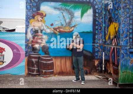 Un homme portant un masque de pigeon regarde son téléphone et envoie un message texte en face d'un carnival ride. Photo Stock