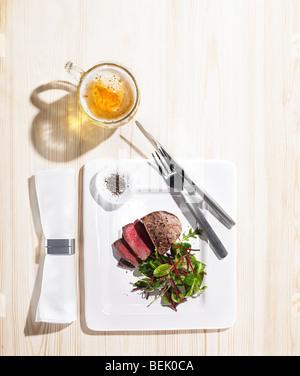 Rôti de bœuf servi avec une salade d'épinards et betteraves, de poivre noir et d'une pinte de Photo Stock